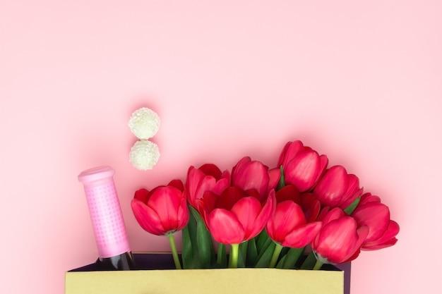 ピンクの背景の紙袋にワインと赤いチューリップと現在の概念。フラット横たわっていた、スペースをコピーします。女性の日、母の日、春のコンセプト。花飾り