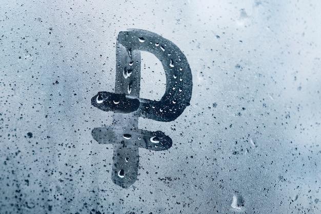 Концепция знака рубля на мокром окне.