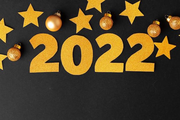 Концепция 2022 года. золотые звезды и числа 2022 года на черной бумаге.