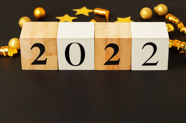 Концепция 2022 года. золотые звезды и числа 2022 года на черном