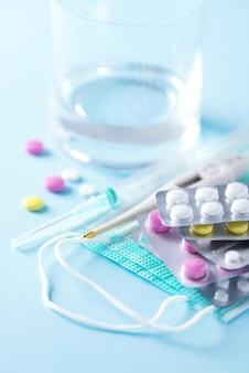 Концепция терапии, профилактика вирусного гриппа, вирусного приступа, таблетки от простуды, антибиотики и витамины, защитные медицинские маски для лица на синем фоне. коронавирус ковид-19. копировать пространство