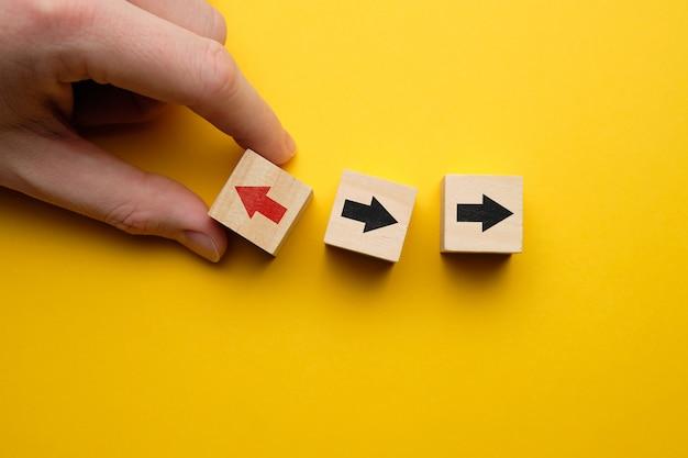 Концепция думать по-другому - рука держит деревянные кубики со стрелками.