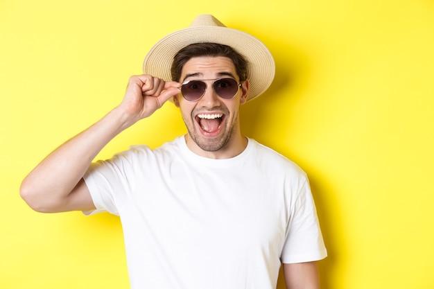 観光と休日の概念。黄色の背景の上に立って、休暇を楽しんで夏の帽子とサングラスで幸せな男のクローズアップ