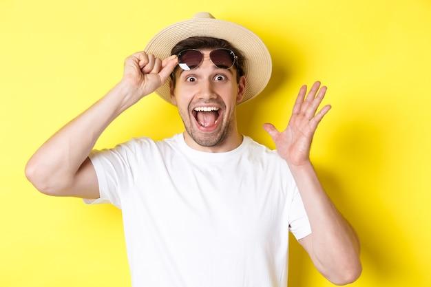관광 및 휴일의 개념. 흥분된 남자 관광 이륙 선글라스와 노란색 배경 위에 서있는 프로모션 제안에 놀란 찾고.
