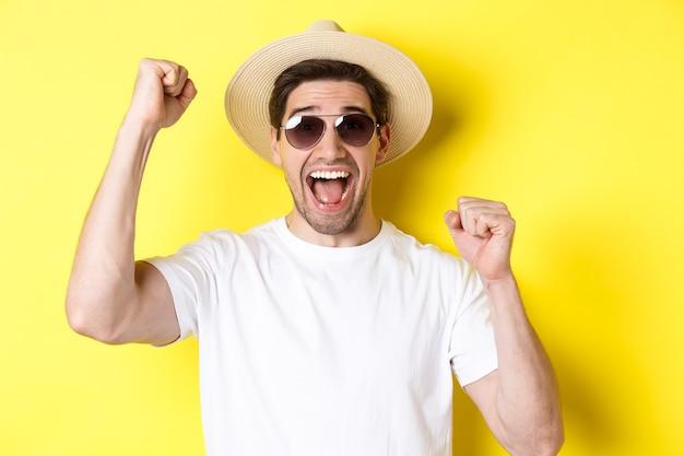 観光と休日の概念彼の休暇を祝う幸せな男性の観光客は手を上げて見せます...