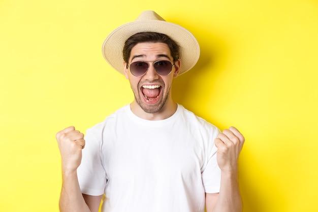 Концепция туризма и отдыха. удачливый турист, выигравший билеты, сжимая кулак и говоря да, одетый в отпускную одежду, стоит на желтом фоне.