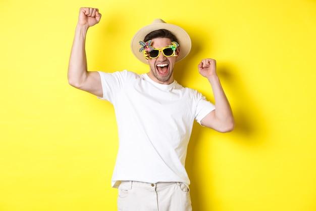 관광 및 라이프 스타일의 개념. 행복 한 운이 좋은 사람이 여행을 승리하고, 기뻐하고 휴가 복장, 여름 모자와 선글라스, 노란색 배경을 착용합니다.
