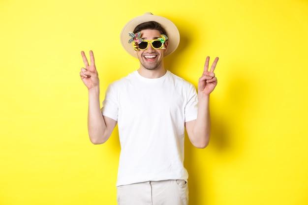 관광 및 라이프 스타일의 개념. 여행을 즐기고, 여름 모자와 선글라스를 착용하고 사진, 노란색 배경에 대한 평화 표지판과 함께 포즈를 취하는 행복한 사람.