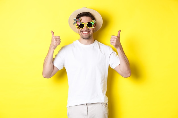 観光とライフスタイルの概念。親指を立てて、旅行を楽しんで、夏の帽子とサングラス、黄色の背景を身に着けていることをお勧めする笑顔の観光客の画像。