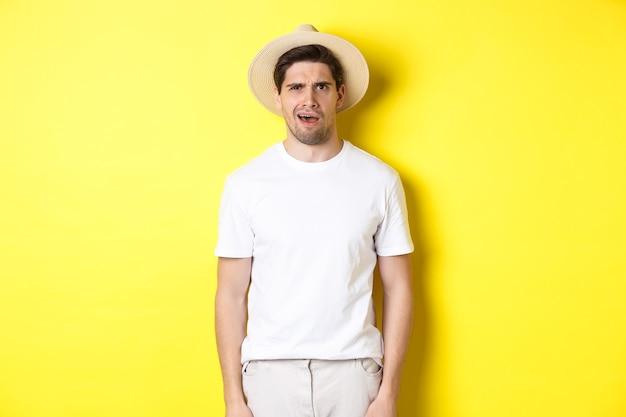 観光と夏のコンセプト。麦わら帽子の混乱した男の旅行者、困惑しているように見える、何かを理解できない、黄色の背景の上に立っている