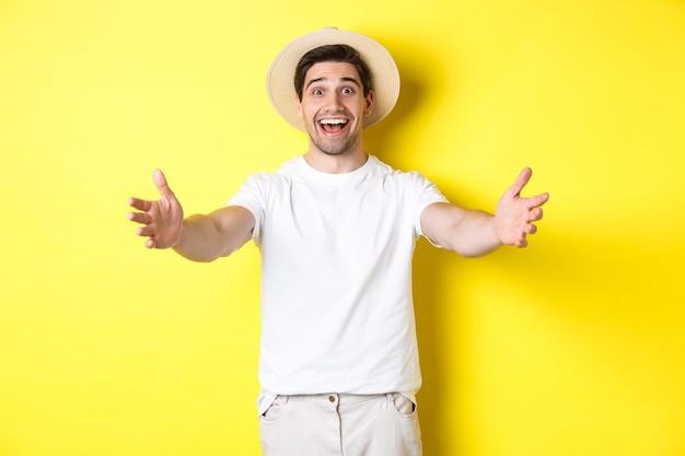 観光と夏のコンセプト。黄色の背景の上に立って、抱擁、挨拶、またはあなたを歓迎するために手を差し伸べる幸せでフレンドリーな男の旅行者