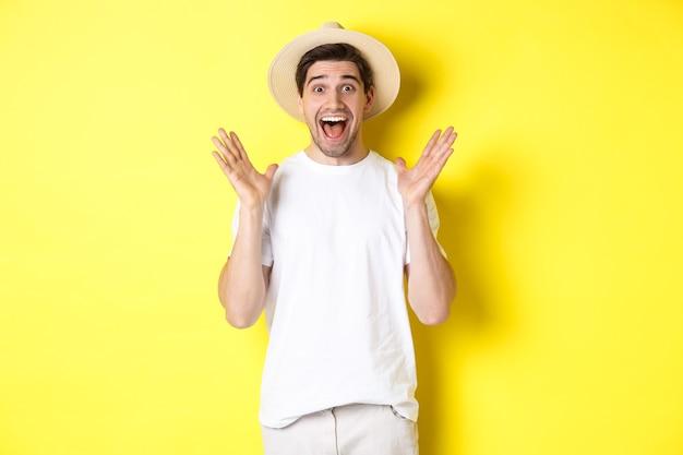 観光と夏のコンセプト。驚いたように見える、驚きに反応して、黄色の背景の上に立っている麦わら帽子の幸せな若い男