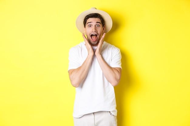 관광 및 여름의 개념입니다. 노란색 배경에 서서 특별 제안에 놀란 밀짚 모자를 쓴 놀란 남성 모델