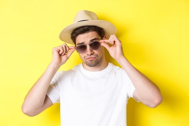 관광 및 휴가의 개념. 밀 짚 모자, 노란색 배경으로 선글라스를 쓰고 여행에 휴가를 즐기는 멋진 관광의 클로즈업.