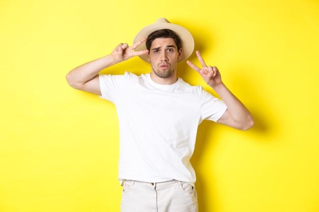 관광 및 휴가의 개념. 휴일에 사진을 찍고, 평화 징후와 함께 포즈를 취하고, 밀짚 모자를 쓰고, 노란색 배경에 서있는 멋진 남자.