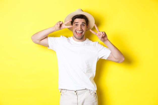 관광 및 휴가의 개념. 행복 한 사람 관광 평화 징후와 사진을 위해 포즈를 취하는 흥분 미소, 노란색 배경에 서.