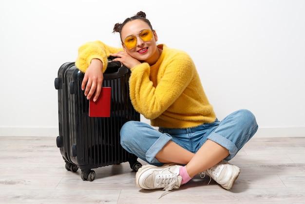 旅行の概念。スーツケースとパスポートを持つ幸せな女の女の子。