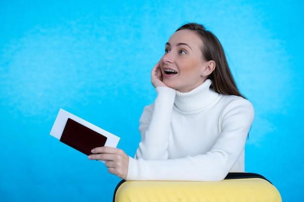旅行の概念。青い壁にスーツケースとパスポートを持つ幸せな女性。