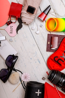 旅行者の概念。パスポート、財布、メガネ、カメラ、bluetoothスピーカー、パワーバンク、イヤホンデバイス、白い木の床。コピースペース