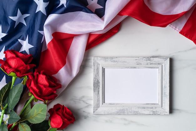 米国独立記念日または記念日の概念。国旗と赤は額縁と明るい大理石のテーブルの背景の上に上昇しました。