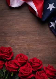 米国独立記念日または記念日の概念。暗い木製のテーブルの背景に国旗と赤のバラ。
