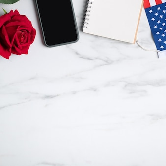 7月4日の米国独立記念日またはメモリアルデーのオンライン販売のお祝いのコンセプト。国旗と赤は大理石のテーブルの背景の上に上昇しました。