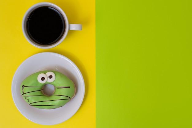 건강에 해로운 다이어트와 간식의 개념. 노란 배경에 분리된 강한 블랙 커피 한잔과 함께 설탕을 입힌 도넛. 녹색 배경, 위쪽 보기에 텍스트 배치