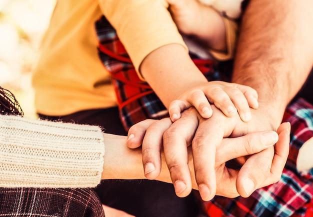 団結、サポート、保護、幸福の概念。両親は赤ちゃんの手を握ります