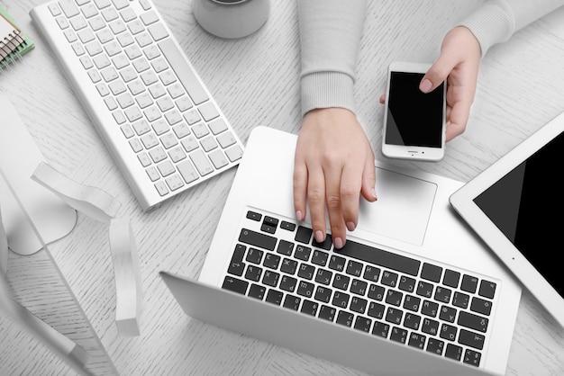 전자 제품 사용의 개념. 사업가 사무실에서 작동합니다. 컴퓨터, 노트북, 태블릿, 커피 한잔 및 테이블에 다른 것들. 평면도