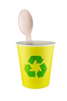 재활용 가능한 재료를 사용하는 개념. 재활용 기호가 있는 종이컵에 있는 나무 숟가락.