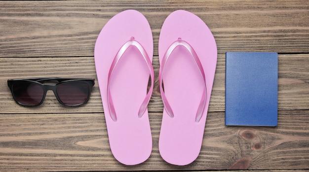 ビーチでの休暇、観光の概念。夏の旅行者の背景。フリップフロップ、パスポート、木製の背景にサングラス。