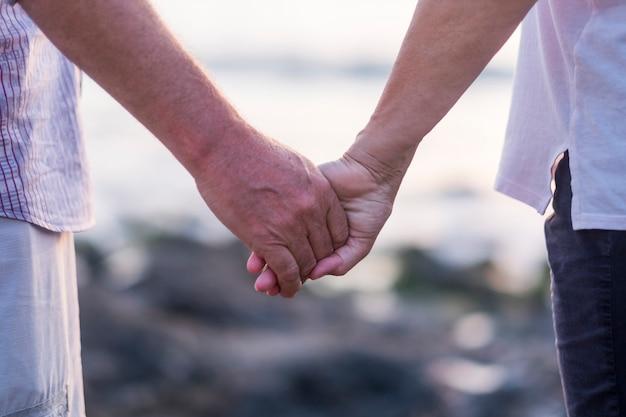 휴가, 관광, 여행 및 사람들의 개념-손을 잡고 행복 한 고위 커플. 평생 함께한 노인들 사이의 영원한 사랑으로 이완과 평온함의 순간