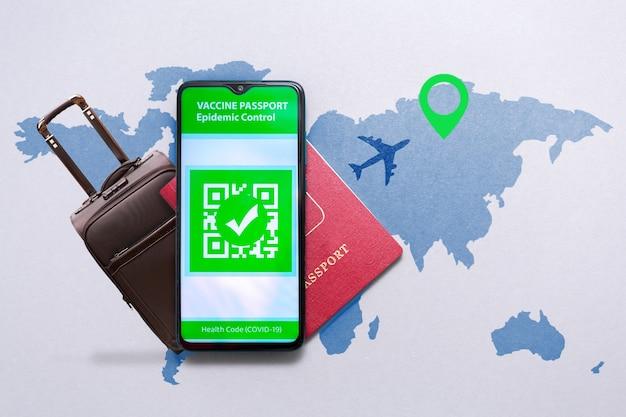 여행 예방 접종의 개념입니다. 스마트폰 화면에 covid-19 백신 스탬프가 있는 전자 면역 여권과 세계 지도에 여권과 여행 가방이 있습니다.