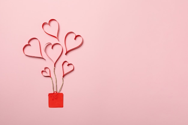 Концепция дня святого валентина с декоративными сердечками и подарочной коробкой на розовом фоне