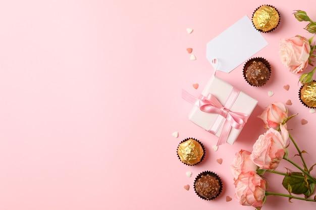 분홍색 배경에 장미, 사탕, 선물 상자와 발렌타인 데이의 개념
