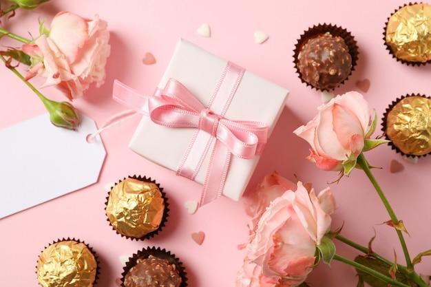 ピンクの背景にバラ、キャンディー、ギフトボックスとバレンタインデーのコンセプト