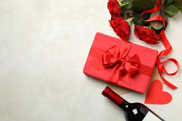 Концепция дня святого валентина с розами, вином и подарочной коробкой на белом текстурированном фоне