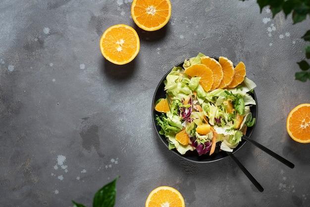 Концепция веганской еды с зеленым салатом и апельсинами, вид сверху с копией пространства