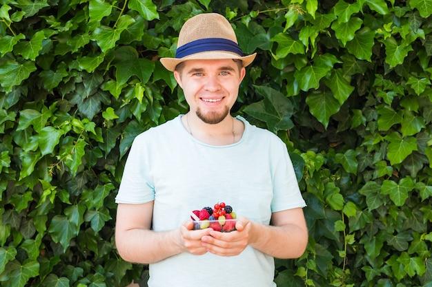 菜食主義者、ローフード、ダイエットの概念-人間のクローズアップは果物とベリーを持っています。