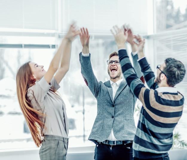 승리의 개념 - ci에 서 있는 기뻐하는 비즈니스 팀