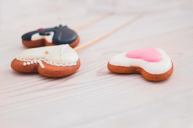 スティック上の白い木製の背景のハート型の生姜クッキーの結婚式の概念
