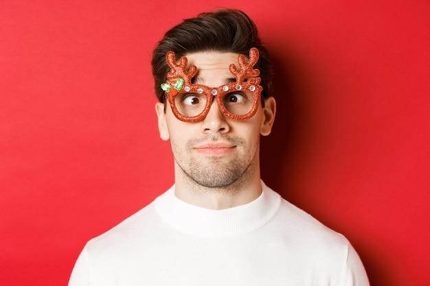 Концепция зимних праздников, рождества и празднования. крупный план смешной брюнетки в партийных очках, щурящейся и гримасничающей, стоя на красном фоне.