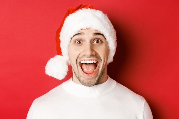 Концепция зимних праздников, рождества и празднования. крупный план удивленного красавца в новогодней шапке, стоящего на красном фоне, слышит удивительное новогоднее промо-предложение