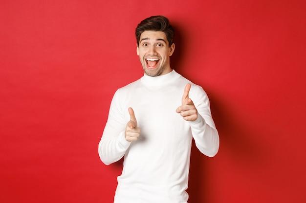 겨울 휴가, 크리스마스 및 라이프 스타일의 개념입니다. 흰색 스웨터를 입은 쾌활한 잘생긴 남자가 당신을 축하하고, 카메라를 손가락으로 가리키며, 새해 복 많이 받으세요, 빨간 배경 위에 서 있습니다
