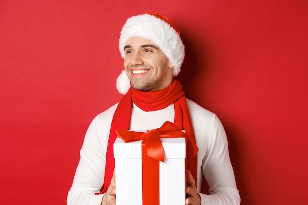 겨울 휴가, 크리스마스 및 라이프 스타일의 개념입니다. 산타 모자와 스카프를 쓴 매력적인 남자가 웃고, 새해 선물을 들고 빨간색 배경 위에 서서 왼쪽을 바라보고 있습니다.