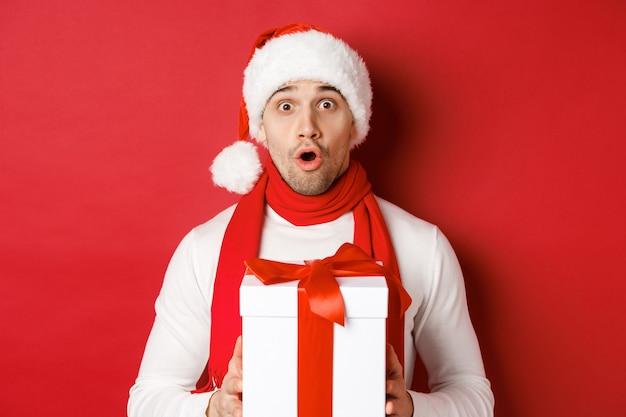 冬休み、クリスマス、ライフスタイルのコンセプト。サンタの帽子とスカーフで驚いたハンサムな男のクローズアップ、驚いて見えると新年の贈り物を保持し、赤い背景の上に立っています。