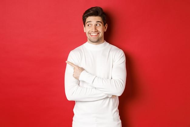 冬の休日のコンセプトクリスマスとライフスタイルは、白いセーターの笑顔でハンサムな男を興奮させました...