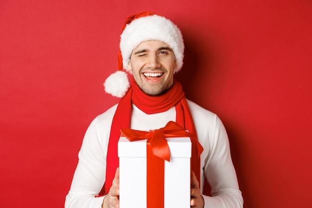 冬休み、クリスマス、ライフスタイルのコンセプト。サンタの帽子とスカーフでハンサムな生意気な男、プレゼントを持って笑顔、カメラでウインク、赤い背景の上に立っています。