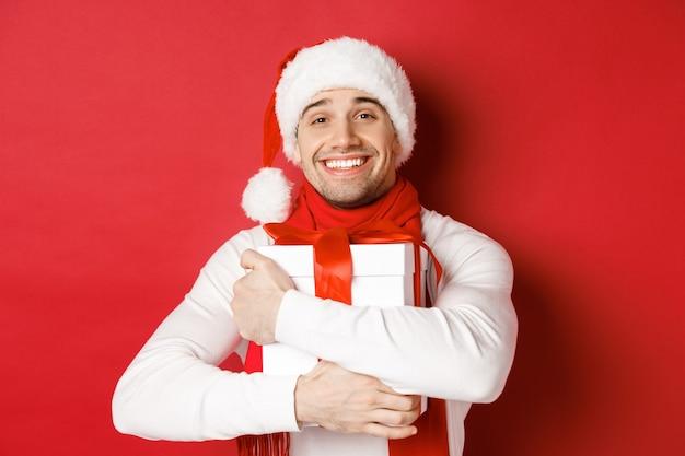 冬休み、クリスマス、ライフスタイルのコンセプト。サンタの帽子とスカーフを身に着けた素敵な男の画像。新年のプレゼントを抱きしめ、赤い背景の上に立って、お世辞を言って笑っています。