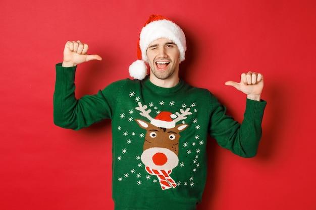 冬休み、クリスマス、ライフスタイルのコンセプト。サンタの帽子と緑のセーターを着た生意気なハンサムな男、自分を指してウインク、赤い背景の上に立っている